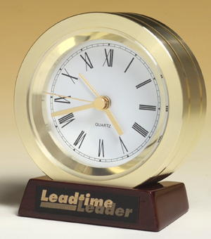 bc917 - solid turned gold aluminum clock on rosewood piano-finished base. black plate, gold color lettering